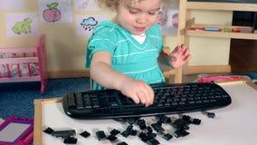 Süßes kleines Kinderjungenmädchen, das mit defekten Tasten spielt stock footage