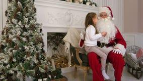 Süßes kleines Mädchen, das auf Sankt-Schoss sitzt und ihn beschreibt, was sie für Weihnachten wünscht stock video