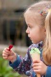 Süßes kleines Mädchen, das Eiscreme isst Stockfoto