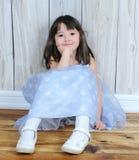 Süßes kleines Mädchen, das mit der Hand auf Kinn sitzt Stockfotografie