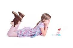 Süßes kleines Mädchen, das mit ihrer Puppe aufwirft Stockbilder