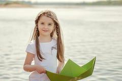 Süßes kleines Mädchen, das mit Papierboot, Nahaufnahme aufwirft Stockfotos