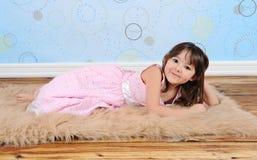 Süßes kleines Mädchen, das playfully auf Pelzwolldecke aufwirft Stockbild