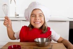 Süßes kleines Mädchen im roten Schutzblech- und Kochhut, der den Chef lernt spielt, Küche zu Hause kochend Stockfotos