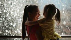 Süßes kleines Mädchen ist, küssend umarmend und ihre schöne junge Mutter Glücklicher Muttertag Wasserfall ist auf Hintergrund stock footage