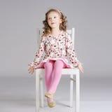 Foto des modernen süßen kleinen Mädchens, das auf dem weißen Stuhl aufwirft Lizenzfreie Stockbilder