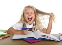Süßes kleines Schulmädchen, das ihr blondes Haar im Druck wird verrückt beim Studieren zieht Lizenzfreie Stockfotografie