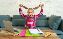 Süßes kleines Volksschulemädchen, das ihr blondes Haar im Druck wird verrückt beim Versuchen zu studieren und Handeln von Hausarb stockfotografie
