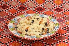 Süßes Kuskus mit Mandel und Trockenfrüchten auf rotem handgemachtem Karpfen Lizenzfreie Stockbilder