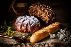 Süßes Laib des Weißbrots pulverisiert mit Zucker, Schwarzbrot, Laib des französischen Brotes auf einem rustikalen Hintergrund Stockbilder