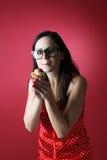 Süßes Leben mit kleinem Kuchen für junge Schönheit auf rotem Hintergrund Stockfoto