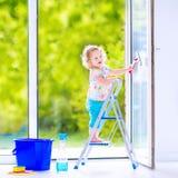 Süßes Mädchen, das ein Fenster im Reinraum wäscht Stockbild