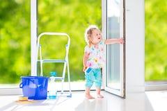 Süßes Mädchen, das ein Fenster wäscht Lizenzfreie Stockfotos
