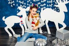 Süßes Mädchen, das mit einem Plüschspielzeug auf dem Hintergrund von Christm sitzt Lizenzfreie Stockbilder