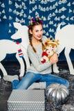 Süßes Mädchen, das mit einem Plüschspielzeug auf dem Hintergrund von Christm sitzt Stockbild