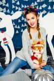 Süßes Mädchen, das mit einem Plüschspielzeug auf dem Hintergrund von Christm sitzt Lizenzfreies Stockfoto
