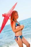 Süßes Mädchen, das mit Regenschirm auf Strand geht. Lizenzfreies Stockbild