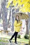 Süßes Mädchen, das mit Regenschirm springt Lizenzfreies Stockfoto