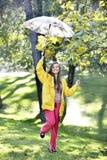 Süßes Mädchen, das mit Regenschirm springt Lizenzfreie Stockbilder