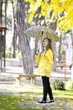 Süßes Mädchen, das mit Regenschirm springt Stockfoto
