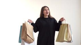 Süßes Mädchen des kaukasischen Auftrittes mit großer Begeisterung, hebt seine Hände ein Bündel Einkaufstaschen an stock video