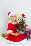 Süßes Mädchen in einem roten Weihnachtskostüm Stockfotos