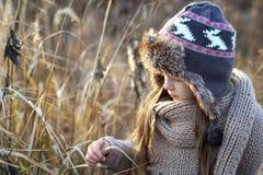 Süßes Mädchen in einer Kappe mit den Rotwild im Herbst auf einem Gebiet des trockenen Grases lizenzfreie stockfotos