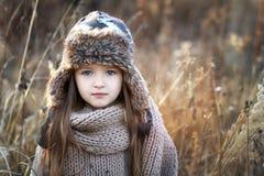 Süßes Mädchen in einer Kappe mit den Rotwild im Herbst auf einem Gebiet des trockenen Grases lizenzfreie stockbilder