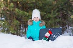 Süßes Mädchen im mit einem Spielzeug Santa Claus New Year zu beglückwünschen Wald, 2017 Lizenzfreie Stockfotos