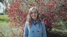 Süßes Mädchen lässt den blühenden Baum mit roten Blumen und geht weiter durch den Park auf einem schönen Frühling spazieren stock video