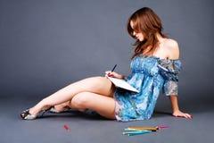 Süßes Mädchen schreiben Gedichte in Notizbuch stockfotos