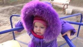 Süßes neugeborenes Baby, das auf Karussell an einem Winter-Tag spinnt 4K UltraHD, UHD stock footage