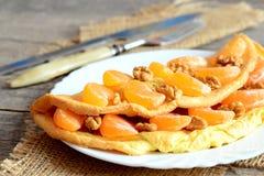 Süßes Omelett auf der Platte und auf Holztisch Gebratenes Omelett angefüllt mit frischen Tangerinen und Walnüssen Stockbild