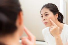 Süßes schönes weibliches Modell, das Spiegel betrachtet Lizenzfreies Stockfoto