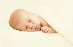 Süßes Schlafbaby, das unter Decke auf dem Bett liegt Stockbilder