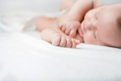 Süßes Schlafen des neugeborenen Babys auf einem weißen Bett Lizenzfreies Stockbild