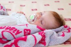 Süßes schlafendes Baby mit soother Stockbild