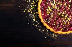 Süßes Törtchen mit Himbeeren, Kirschen, rote Johannisbeeren mit Pistazien, Puderzucker auf dunklem hölzernem Hintergrund Copyspac Stockbilder