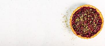 Süßes Törtchen mit Himbeeren, Kirschen, rote Johannisbeeren mit Pistazien, Puderzucker auf weißem konkretem Hintergrund Stockfotos