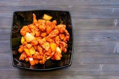 Süßes und saures Huhn in der schwarzen Schüssel auf dunkler Tabelle lizenzfreie stockfotografie