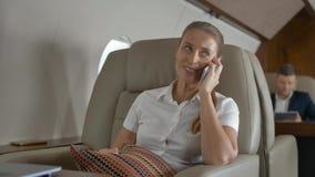Süßes weibliches Sprechen über Luxusreiseinnere des Privatjets stock footage