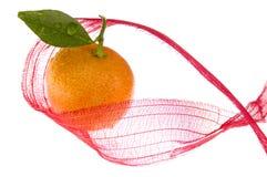 Süßes Weihnachten. orange Frucht und roter Bogen Stockfoto