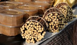 Süßholzwurzeln gebunden und transparente Behälter des Süßholzextraktes Engagiertes Regal in einem lokalen Markt stockfotografie