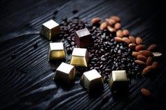 Süßigkeit in der goldenen Folie, in den Mandeln und in den Sonnenblumensamen in der Schokolade, die auf einem dunklen Hintergrund Stockfoto
