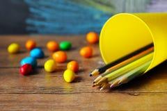 Süßigkeit und farbige Bleistifte Lizenzfreies Stockfoto