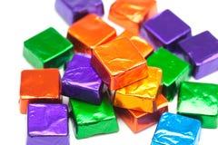 Süßigkeiten in den glänzenden Verpackungen getrennt auf Weiß Lizenzfreies Stockfoto