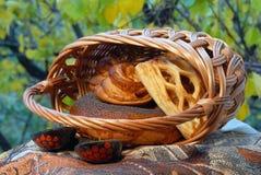 Süßigkeiten in einem Weidenkorb gegen einen Hintergrund des grünen Laubs stockfotos