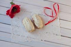 süßigkeiten Zwei Eclairs und rotes Band auf Holztisch Beschneidungspfad eingeschlossen Lizenzfreie Stockbilder