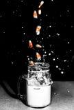 Süßigkeits-Mais, der im Milch-Glas spritzt Stockbilder
