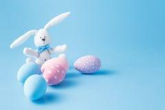 Süßigkeitsfarb-Ostereier mit Kaninchen über Minze Stockbilder